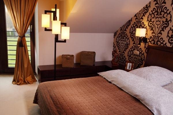 Sypialnia na poddaszu oświetlona klimatycznymi lampami Manhattan firmy Technolux
