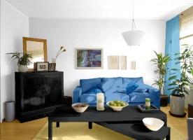 Jak rozjaśnić pokój z czarnymi meblami i niebieską kanapą?