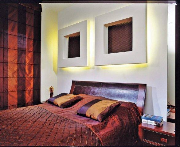 Dekoracją ściany są dwie ramy zrobione z płyty g-k. Ich środki wykończono tynkiem strukturalnym pomalowanym farbą. Za ramami jest oświetlenie zastępującego lampki nocne.