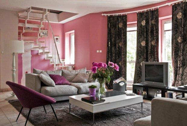 Aneks wypoczynkowy w salonie. Na tle różowych ścian szare kanapy wyglądają ciekawie i elegancko
