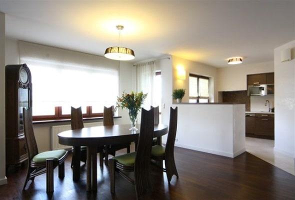 Salon połączony z kuchnią oświetlaja lamp z tej samej serii. Projekt Studio Zero