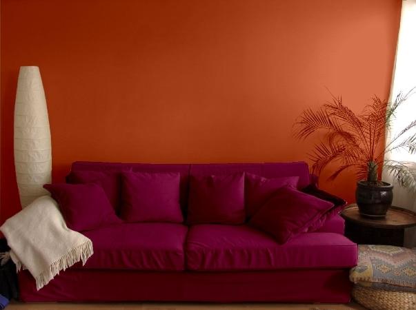 Pomarańczowa ściana w zestawieniu z ciemnoróżową kanapą