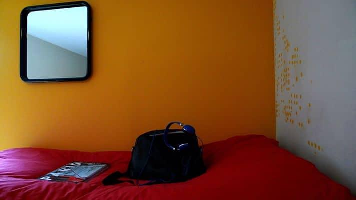 Czerwona kanapa na tle pomarańczowej ściany