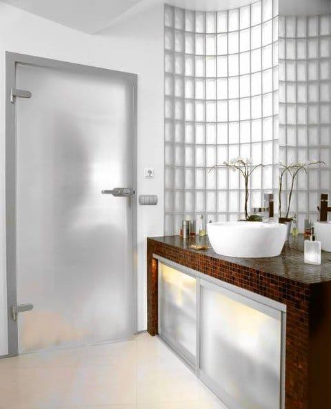 Za przesuwanymi drzwiczkami - zrobionymi z tafli matowego szkła w aluminiowych ramach - kryją się ręczniki, płyny i proszki. Dzięki podświetleniu prosta skrytka zyskuje walor dekoracyjny. Rozproszony blask dodaje łazience ciepła.