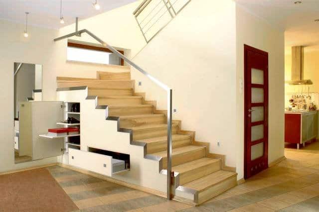 Pod schodami są schowki na obuwie. Dzięki wysuwanym półkom łatwo się dostać nawet do najgłębiej ustawionych butów.