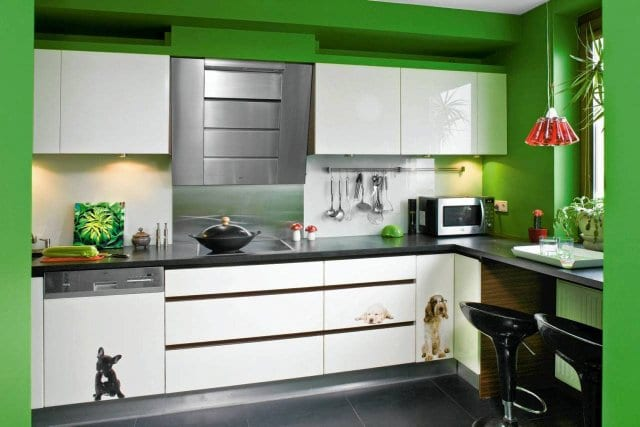 Białe meble kuchenne połączono z zielonymi ścianami