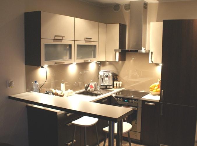 Mała kuchnia z barkiem; na ścianie nad blatem szkło lacobel. MM-kuchnie.pl