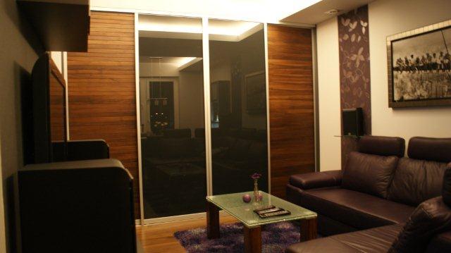 Pokój dzienny z całkowicie zabudowaną ścianą. Projekt Quadrat. Wykonanie MM Kuchnie