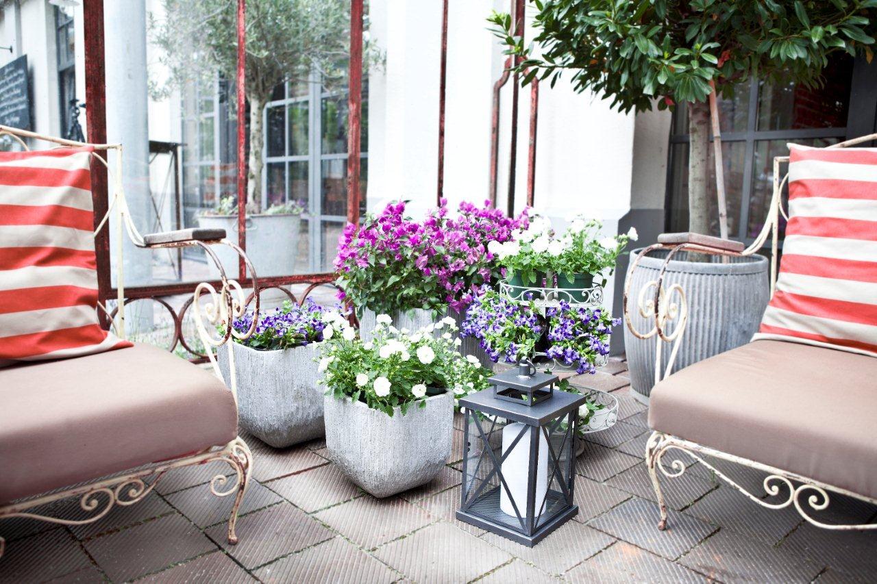 Dekoracja balkonu - kwiaty w ceramicznych osłonkach i lampiony. Westwing.pl