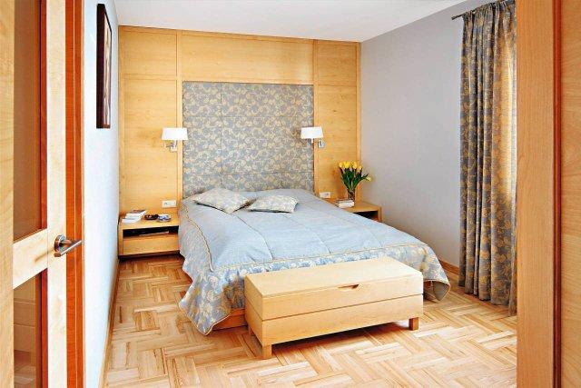 Ścianę za łóżkiem wyłożono panelami fornirowanymi brzozą, gąbką i pikowaną tkaniną. Z tej samej tkaniny jest uszyta narzuta na łóżko i poduszki dekoracyjne.
