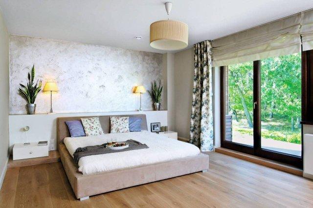 Ścianę za łóżkiem wykończono tynkiem strukturalnym. Konstrukcja za łóżkiem pełni funkcję półki na kwiaty doniczkowe i lampki
