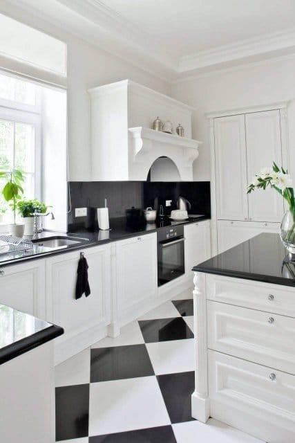 W czarno-białej kuchni blat jest z granitu. Kamień pojawia się również na fragmencie ściany. Na podłodze kafle polerowanego gresu. Zdjęcie www.czterykaty.pl