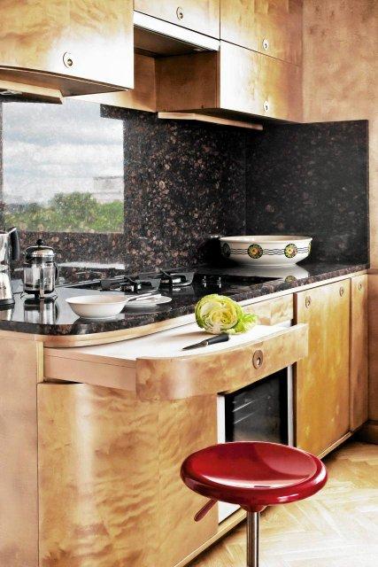 Granitowy blat doskonale pasuje do drewnianych mebli. Granitem wyłożona jest też ściana nad blatem. Zdjęcie www.czterykaty.pl
