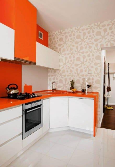 Energetyczny, pomarańczowy blat z płyty laminowanej jest bardzo efektownym rozwiązaniem. Z tej samej płyty zbudowano bok zabudowy. Zdjęcie www.czterykaty.pl