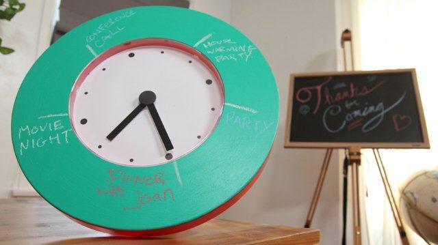 Zegar udekorowany napisami na powierzchni pomalowanej farbą tablicową