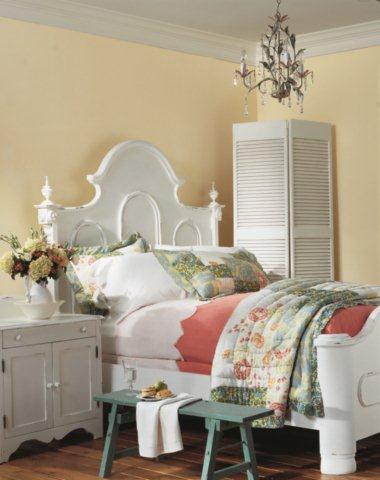 Białe zdobione meble w sypialni na tle piaskowych ścian