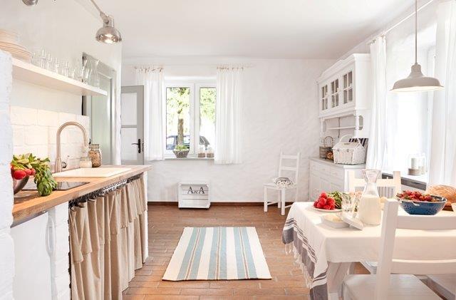 Biała kuchnia z drewnianymi blatami; zamiast frontów powieszono zasłonę z grubej tkaniny- Jola Skóra/MAKATA, stylizacja A&A Bath