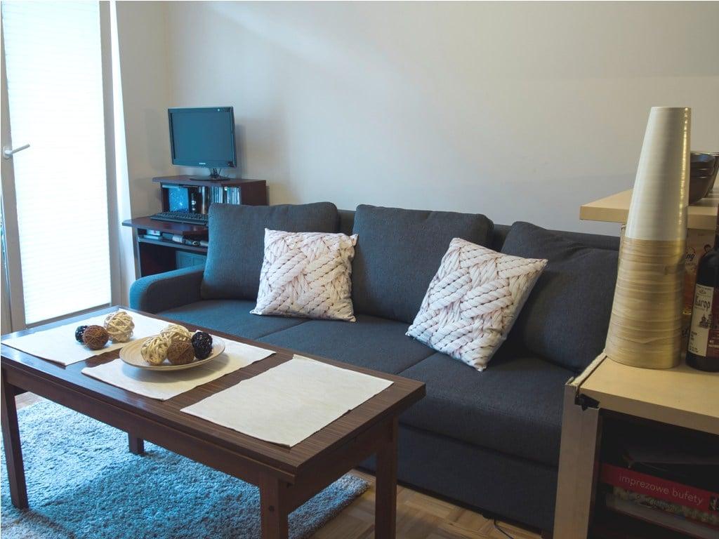 Pokój po metamorfozie - nowa kanapa, zamiast ciężkiego mebla obok kanapy stoik stolik komputerowy. Jasne poduchy i dodatki rozświetlają wnętrze
