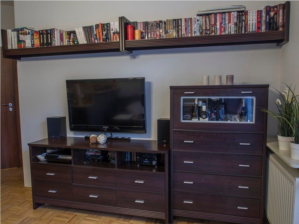 Dwie półki w równiej linii nad telewizorem porządkują układ mebli