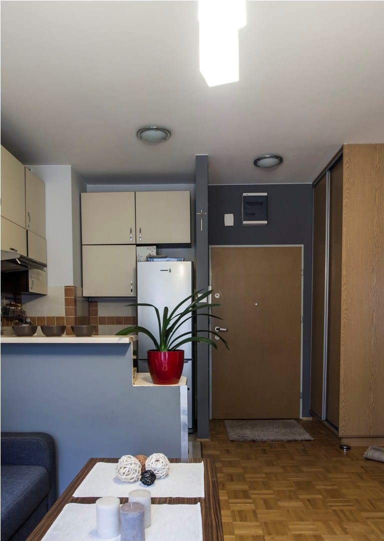 Ciemne szare ściany wokół drzwi wejściowych mają ten sam odcień, co ścianka oddzielająca kuchnię od pokoju
