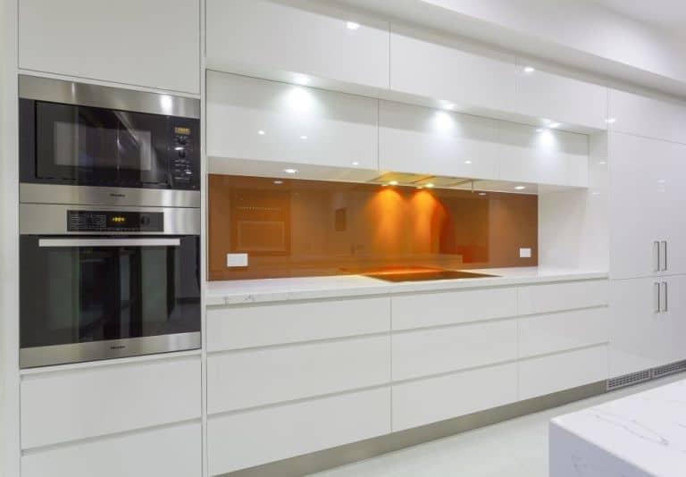 Białe meble kuchenne i szkło labocel nad blatem - oświetlenie na kilku poziomach - fot. shutterstock