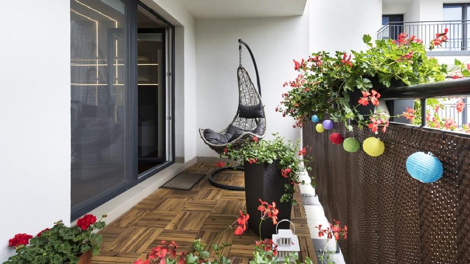 Balkon z fotelem bujanym i kwiatami