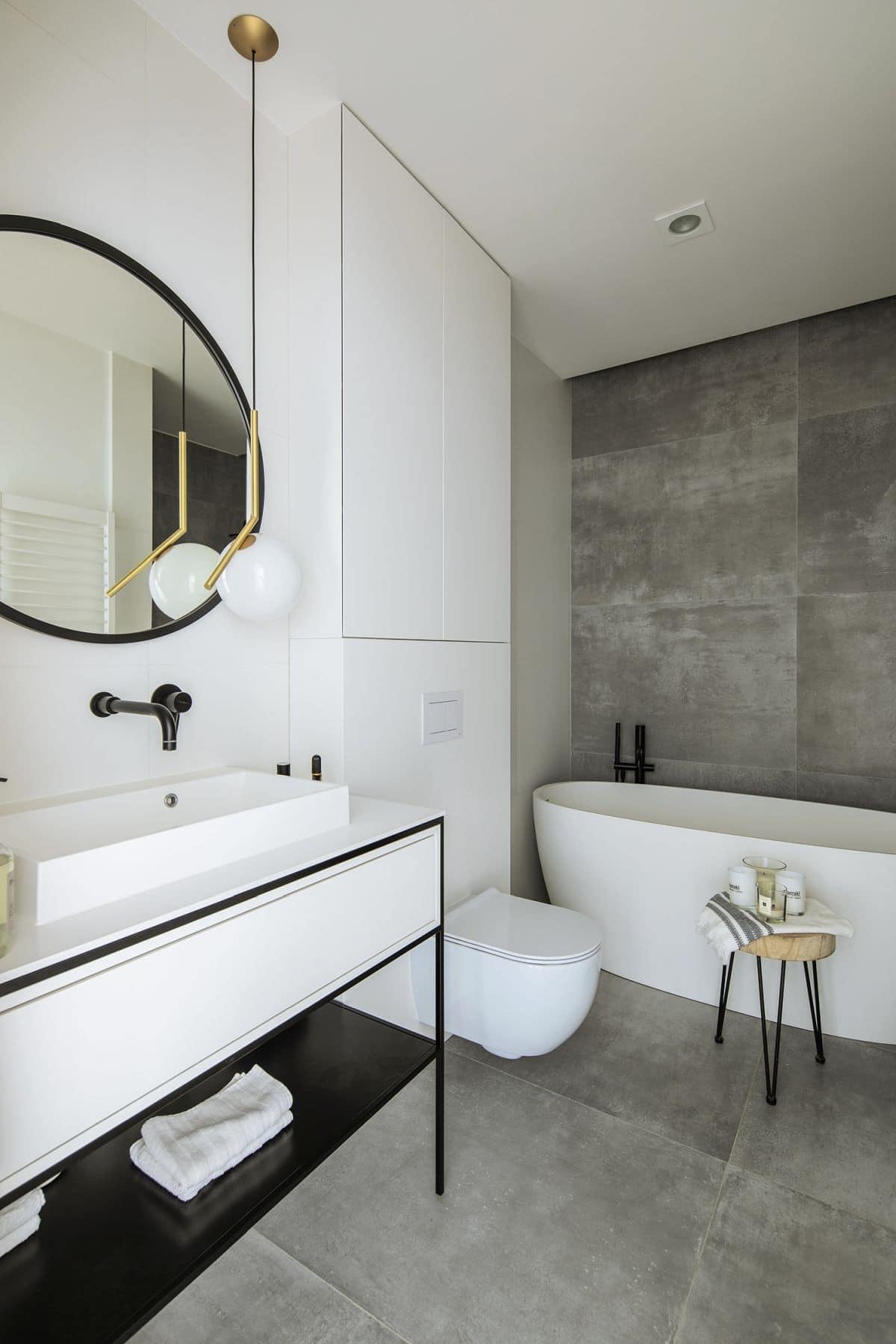 W łazience powierzchnie ścian i podłoga są wykończone imitacją betonu