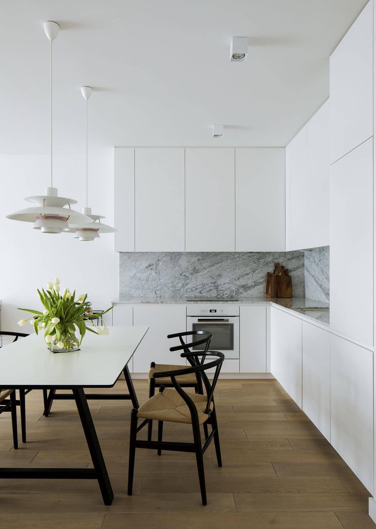 monochromatyczna zabudowa kuchenna w duecie z marmurem na ścianie